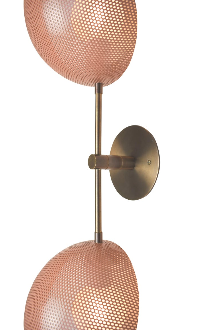 The Axial sconce conveys a strong modern design defined by balance and equilibrium. Axial features two bowl-shaped shades fabricated of spun metal mesh, tilted at an angle, mimicking the axial tilt of the planets in orbit. This line, designed in