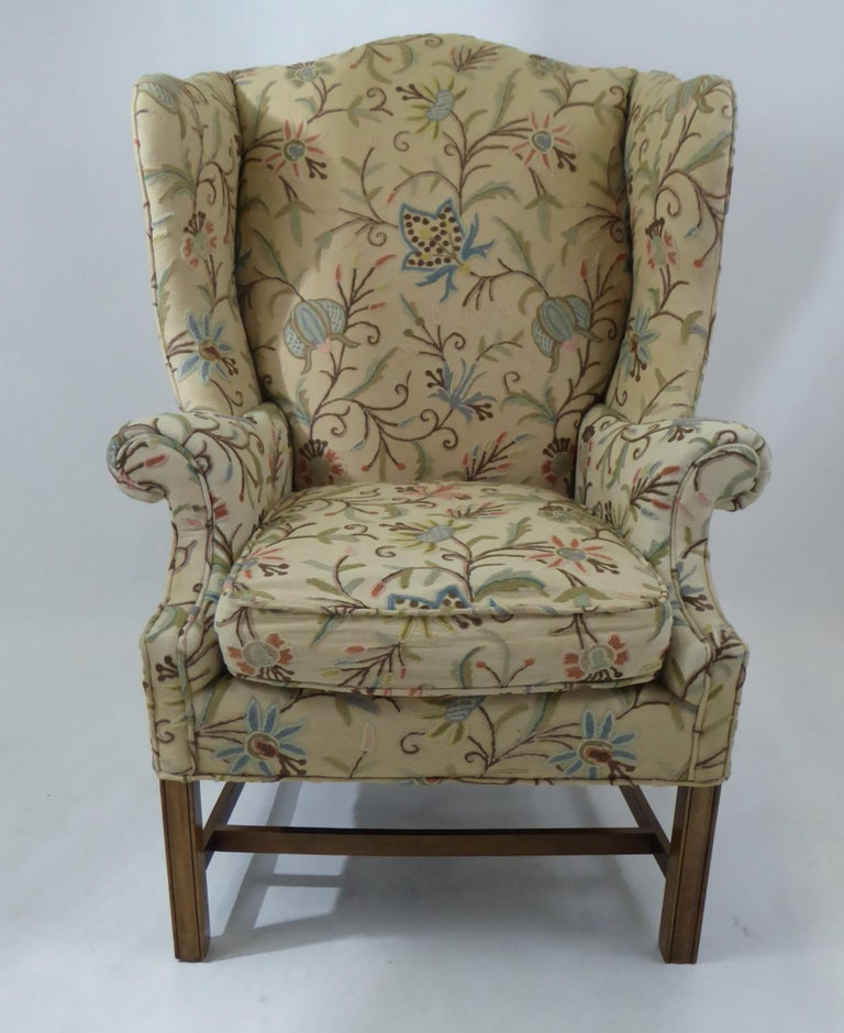 A wonderful 1950s era Baker Chippendale style wingback in a multicolor Crewel stitched fabric. Lovely floral motif in the crewel stitching, beautiful dark wood legs, great deep wings and curves. Some scratched fabric/ worn area on back left side