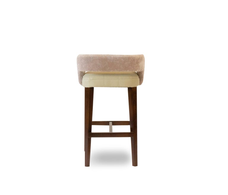 Our Bouche stool is a custom height bar stool. Shown in a sophisticated Romo vinyl with Romo velvet on the back, the legs are a stained maple with a brass kick. Fabrics and finish are customizable. Made in our Connecticut workshop. These are made to