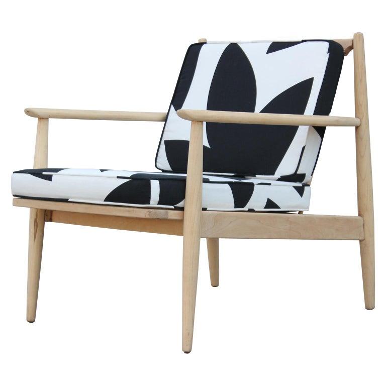 A beautiful modern Danish style lounge chair featuring a playful geometric black and white pattern fabric and a custom light walnut finish. By Baumritter.