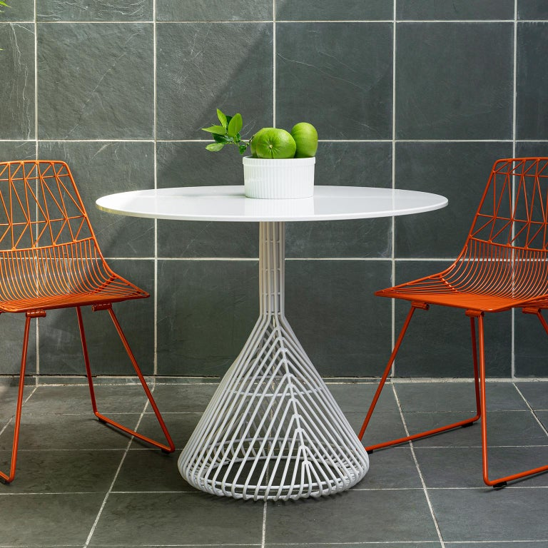 Bend Goods wire furniture This modern wire dining table updates the outdoor bistro shape with a tightly knit base that is durable and sculptural. The bistro table is a callback to a Classic design with a contemporary twist that works inside or