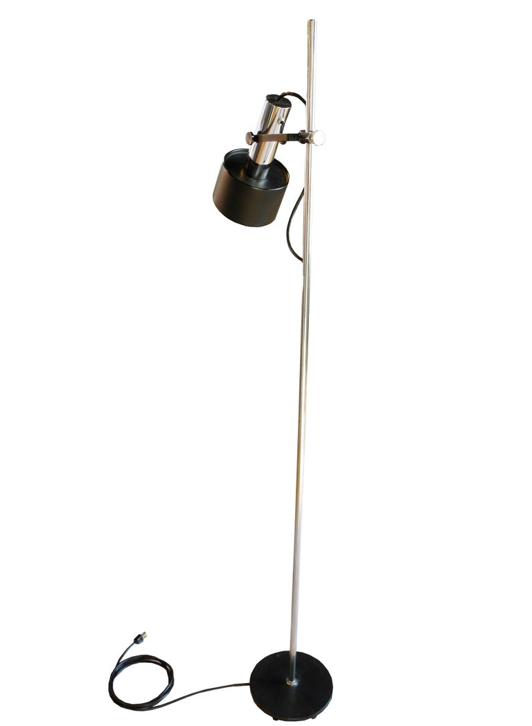This modern adjustable versatile floor lamp goes up and down the rod and swivels all around on the arm. The lamp has a weighted iron base and works perfectly.