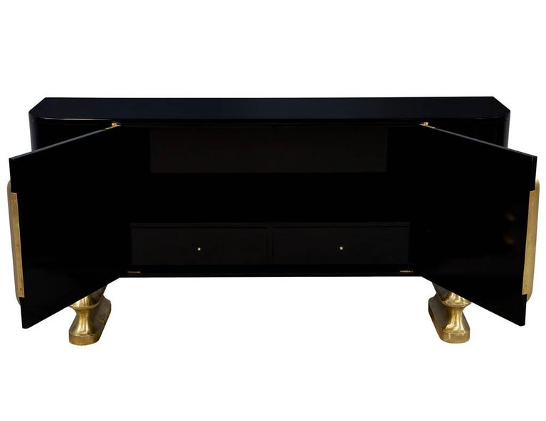 Modern polished black lacquer sideboard credenza. Featuring curved sides with slotted brass hardware, sitting on two unique one of a kind flowing brass bases. Complimentary curb side delivery included to the continental USA.