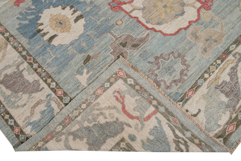 Beautiful modern Sultanabad hand knotted wool rug with a blue field. This Sultanabad rug has an ivory frame and a multi-color accent in a gorgeous all-over Classic floral medallion design.  This rug measures: 10'4