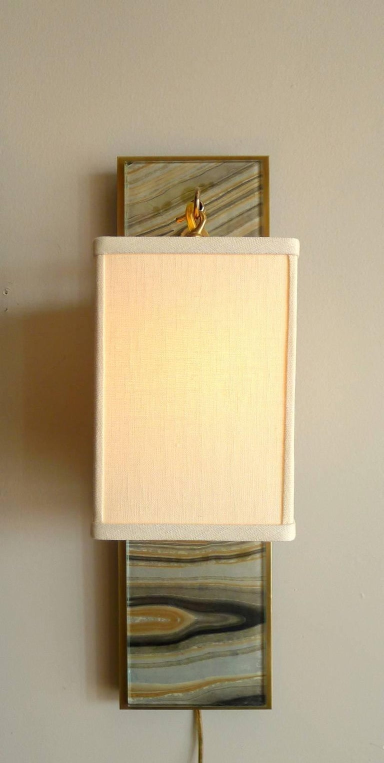 "Modern brass and marbleized wall sconce V2 by Paul Marra. Glass over marbleized paper. Brass. Linen shade shown. Projection is 8"". Refer to photos for variation in colors from turned on verses not lit