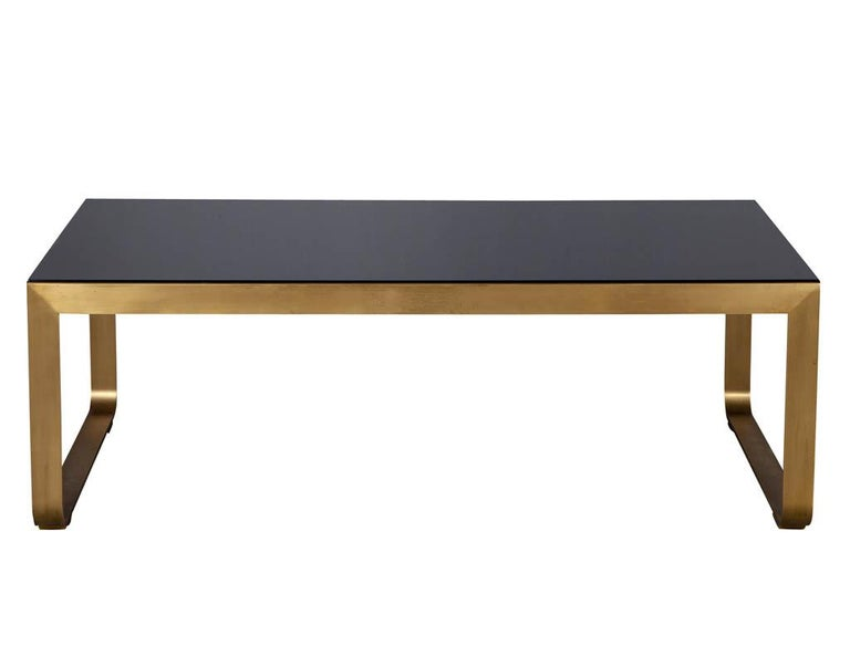 Modern brass cocktail table by Baker Furniture. Featuring sleek brass pedestal and high gloss black wood top.  Price includes complimentary curb side delivery to the continental USA.