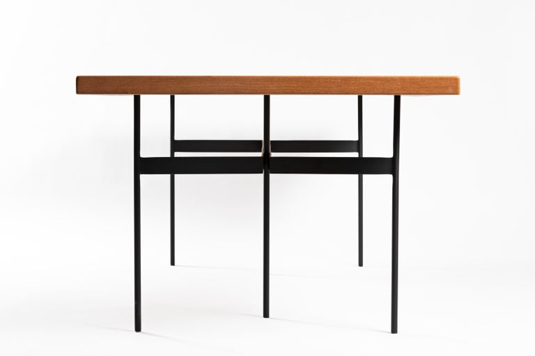 This contemporary Brazilian dining table is made in a minimalist style with solid steel and wood, which lends a simple and powerful design. The table has an architectonic and geometric reasoning, rectangular bars are welded to the circular supports