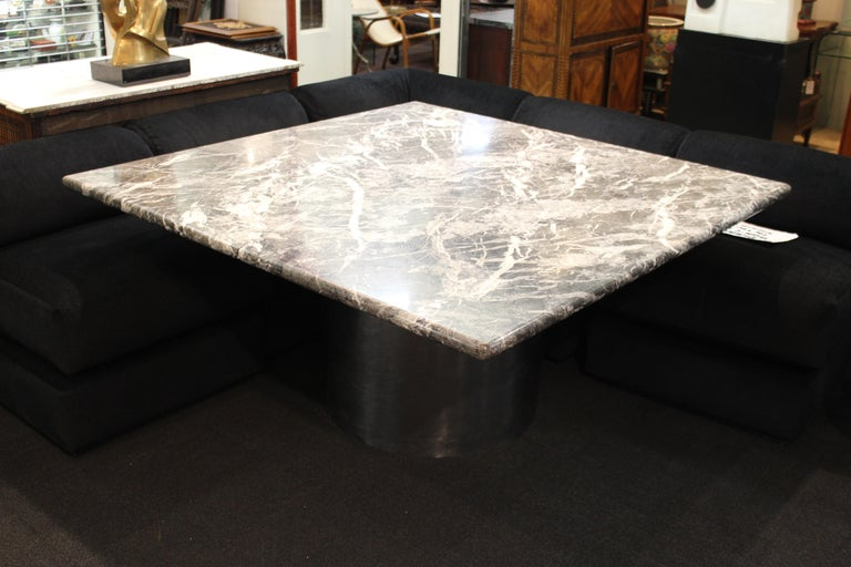 Modern custom made dining table or center table, custom made with a heavy square veined dark marble top on a circular chromed metal base. The piece is in the style of Brueton and was likely custom made during the late 20th century. In great vintage