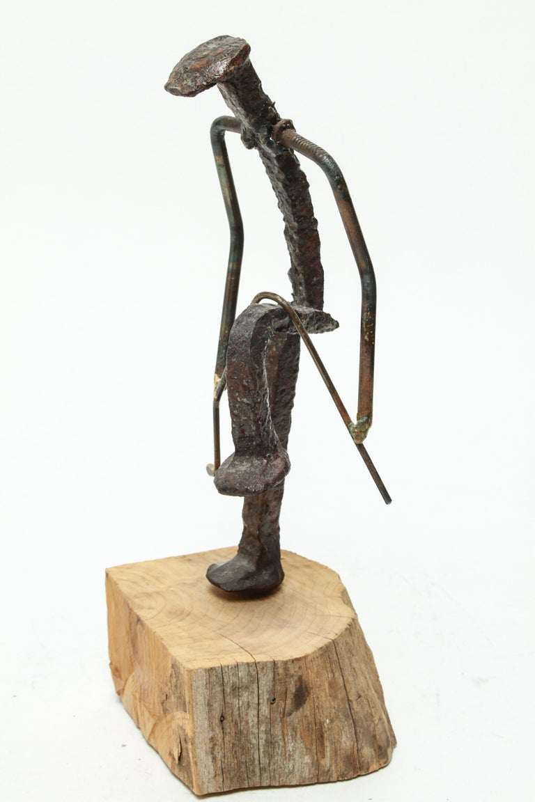 Brutalist modern sculpture of a golfer breaking his golf club over his knee. The piece is made of iron nails, atop a natural wood base. In great vintage condition with minor age-appropriate wear.