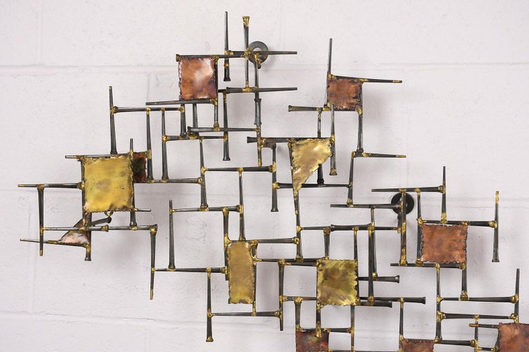 This is a 1960s midcentury Brutalist style brass, metal, wall sculpture features varying sized geometric shapes on a woven into a forged nail base. This sculpture is intriguing, sturdy, and ready to be hung on any wall for years to come.