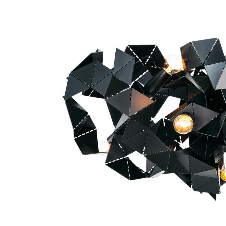 The Fractal, a modern chandelier in black matt finish, is designed by William Brand, founder of Brand van Egmond. The play between the unexpected geometry of the surfaces and the characteristics of the metal changes the light from every point of