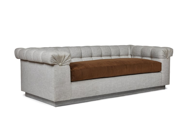 The Martin & Brockett Chester sofa is a modern take on the chesterfield. A biscuit-tufted upholstery frame with loose bench seat and a pleat and button detail on each arm. The base is a three-inch oak plinth in cerused nimbus gray. Other base