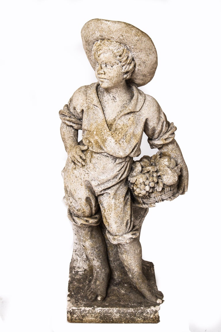 Modern pair of cement garden sculptures depicting two young boys. One boy is holding a basket of fruit and one is holding wheat. The pair is in great vintage condition with age-appropriate wear and use.