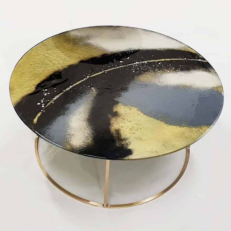 Contemporary and modern round coffee tables with Murano kind handmade glass colored using metal oxides in black and grey and liquid metal in gold color. Limited collection signed by Edith Baranska. Each piece is unique and a bit different due to the
