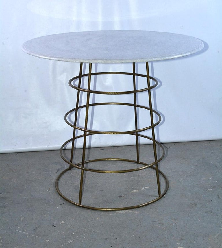 Stylish gilt metal bistro or pub table with white marble top has a metal base with 4 graduated rings. Table can work well in a modern, traditional or casual setting. Can be used indoors or outdoors. Garden, porch or poolside patio table.