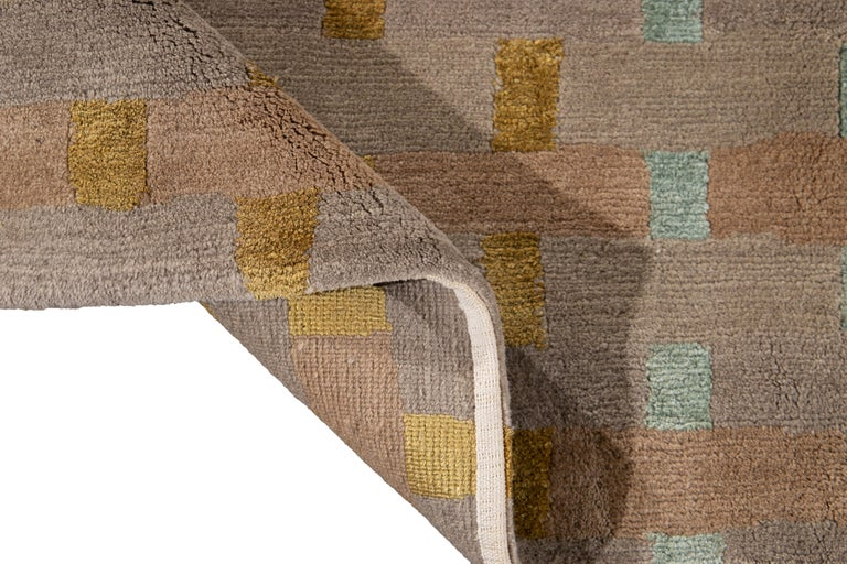 Beautiful Modern Tibetan hand knotted Wool rug with the tan field. This rug has accents of goldenrod and green in a gorgeous all-over geometric design.  This rug measures: 9' x 12'.