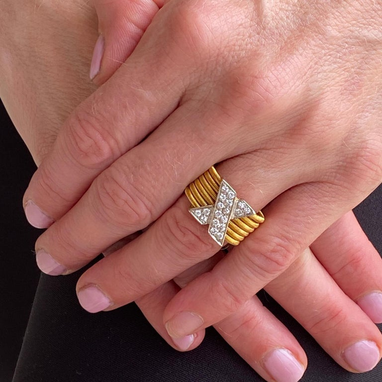 This stylish diamond X ring is crafted in 18 karat yellow and white gold. The white gold X features 18 round brilliant cut diamonds weighing approximately .50 carat total weight and graded G-H color and VS clarity. The 6 row woven yellow gold band