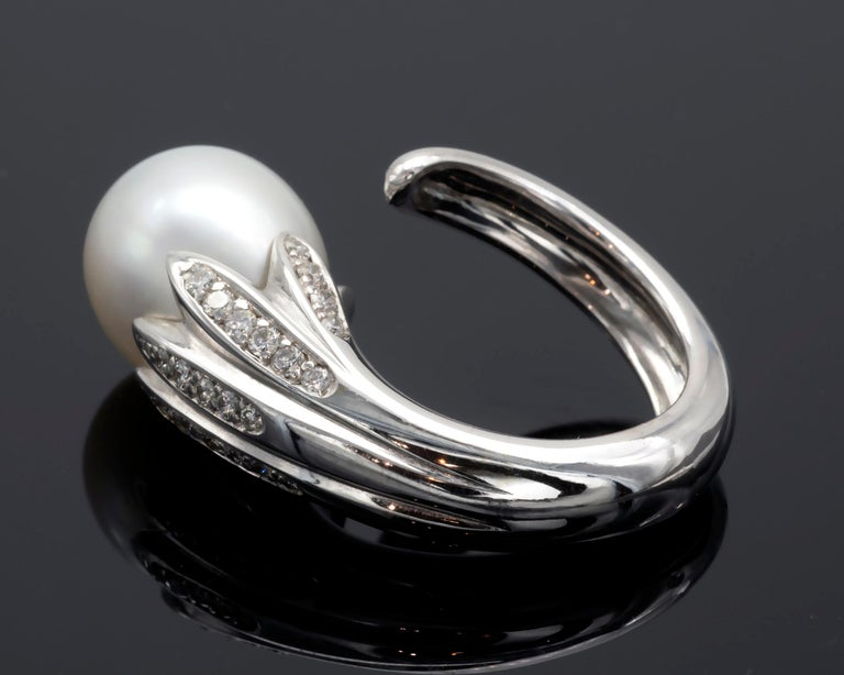 Amazing pearl ring: the 18 KT white gold shank wraps around the finger like a stem from which leaves, set with diamonds, hold a beautiful drop shaped south sea pearl measuring 12x15.5mm. The ring is very well made weigh nicely in the hand,  French