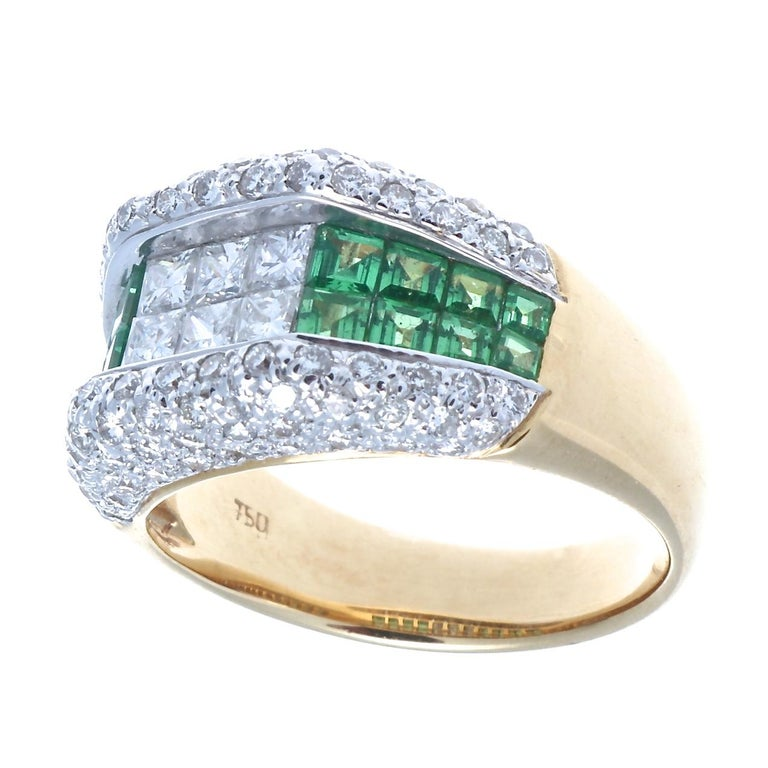 Classic modern architecture featuring color and geometric design resulting is a sparkling presentation. The ring is built with rows of near colorless diamonds and vibrant green demantoid garnets. Crafted in 18k white and yellow gold.