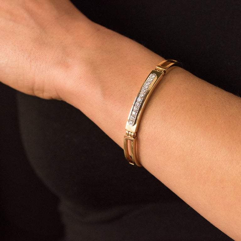 Bracelet in 18 karats yellow gold, eagle's head hallmark and platinum, dog's head hallmark. This beautiful bracelet is composed of 3 curved elements and articulated between them by solid dowels. On the bottom pattern, a line of 12 brilliant-cut