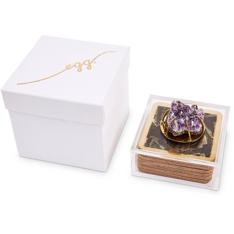 These modern brass coasters are etched with a snakeskin animal pattern and are presented in a Lucite box decorated with a Rose Quartz Agate cabochon.   This unique and bespoke coaster set is part of the Egg Designs Dawa luxury bar set collection