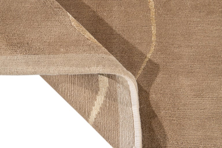 Beautiful modern Tibetan hand knotted wool rug with the tan field. This rug has accents of beige in a gorgeous all-over abstract expressionist design.  This rug measures: 9' x 12'.