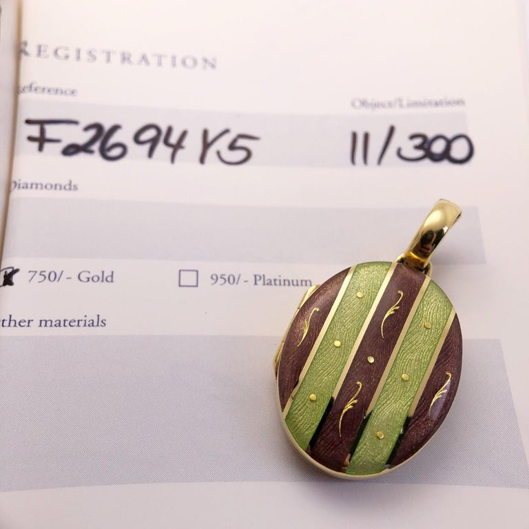 This Modern Faberge 18 Karat Yellow Gold oval locket is adorned with Purple and Green Guilloché Enamel stripes. The 18 Karat yellow gold bale opens allowing you to attach the locket on to various strands. The locket opens and contains two removable