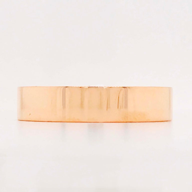 This modern flat rose gold band ring is a unique design with a modern structure. The band is a flat style with a high polish finish. The band is 5 mm wide and made with a rich 14 karat rose gold! The rose gold has a traditional copper-like color
