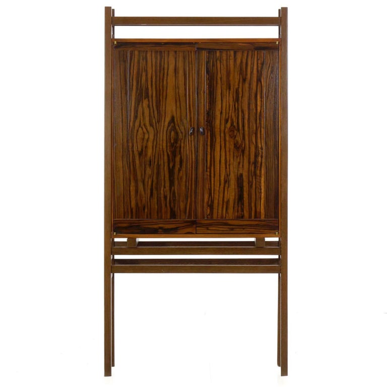 An exquisite work of visual simplicity against technical mastery. This fine cabinet is crafted of mahogany, ebony and wenge each set against one another in perfect balance. The Macassar in the doors has a dramatic grain full of movement, these