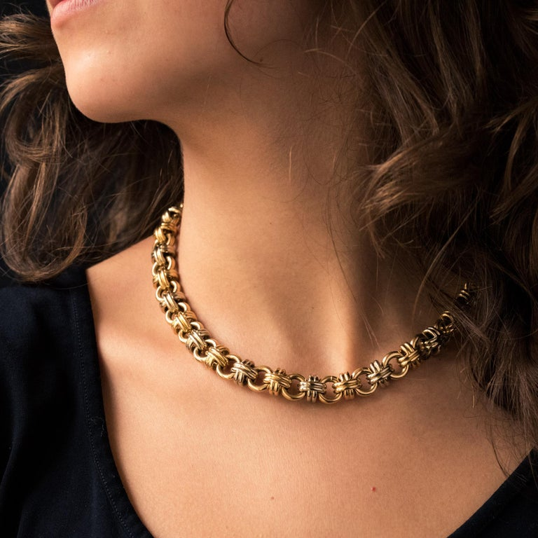 Necklace in 18 karat yellow and white gold, eagle's head hallmark. Round swirling necklace held in place by alternating white and yellow gold knots. The clasp is ratchet with safety