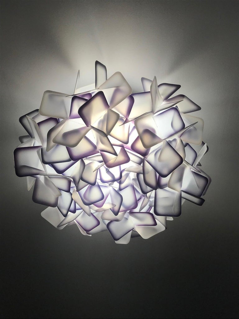 Exquisite ceiling light or wall sconce comprised of multifaceted interlocking resin squares. The square clusters are made of the patented Opalflex developed through the recycling of technopolymers and glass crystals. The resin squares are frosted