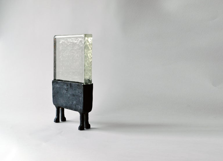 Luminaire No. 2 J.M. Szymanski d. 2019  Luminaire No. 2 is created out of cast glass and blackened steel creating a striking table lamp. The unusual geometries and heavy matrial textures make this lamp a extremely special and one of a kind.