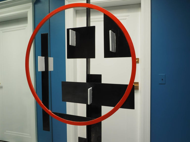 Modern geometric steel sculpture, painted metal with tall black central support, added red circle, and black panels with attached white elements. The black base mounted on a tiered ebonized wood platform.   Condition: some wear to the paint on the
