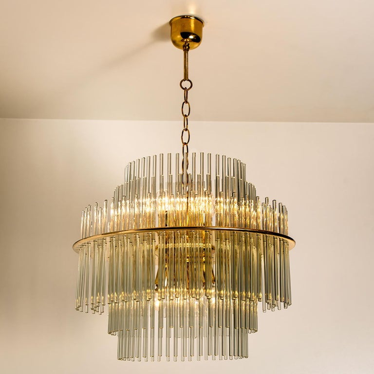 Clean lines to complement all decors. Wonderful high-end light fixture for Lightolier. With brass detail and 192 hanging waterfall glass giving the piece an elegant appearance which refracts the light, filling a room with a soft, warm glow  The