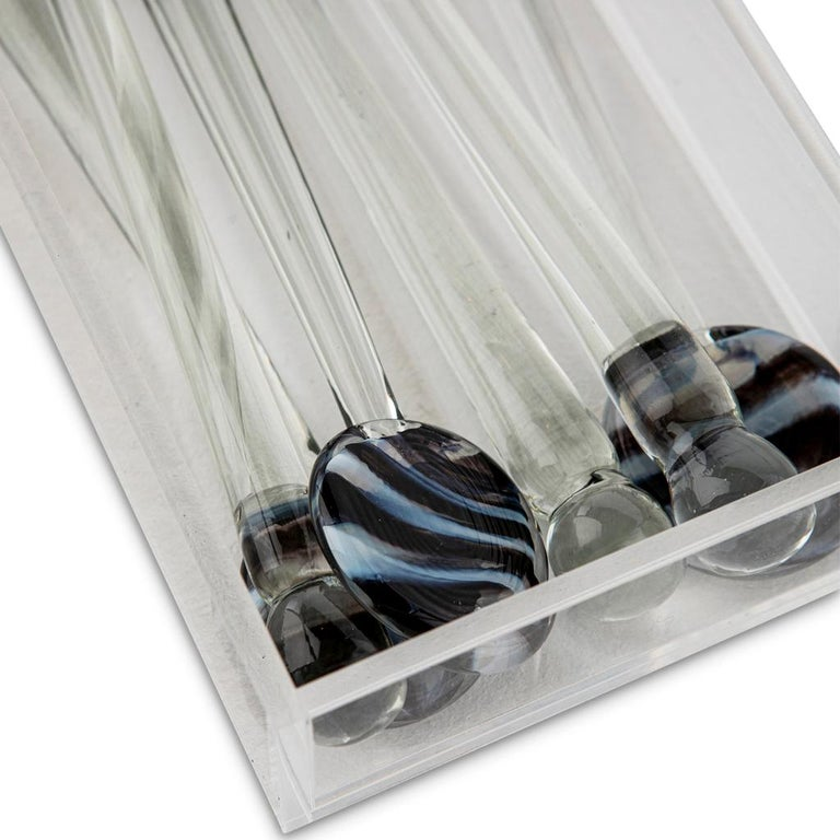 These modern hand forged glass swizzle sticks have a clear glass stem with zebra striped glass heads. They are presented in a Lucite box decorated with a Rose Quartz Agate cabochon. 