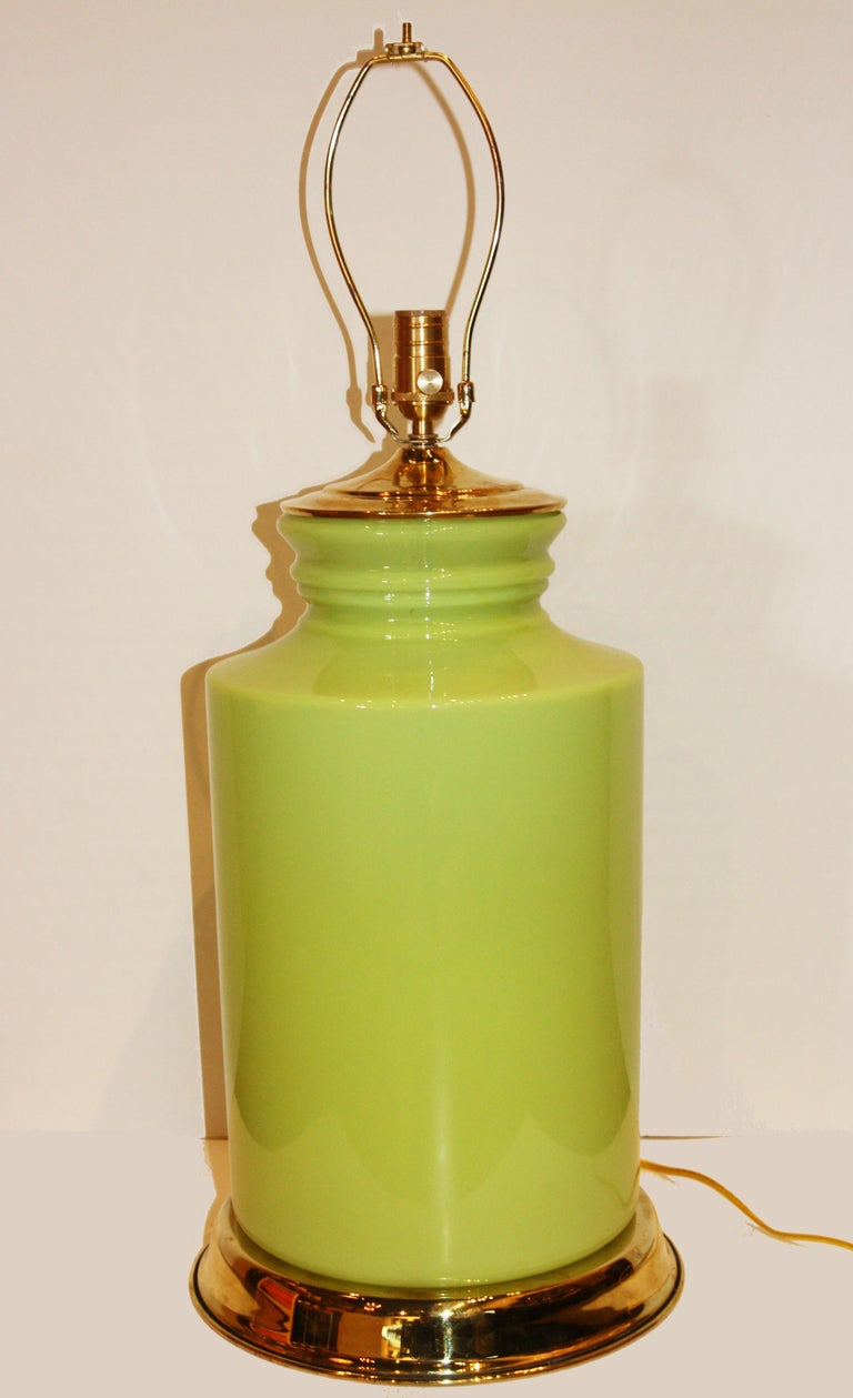 This is a green, porcelain lamp with a modern shape and brass accents. Fully functional, shade not included.