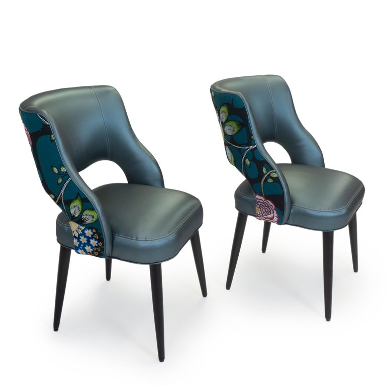 This new dining chair design is comfortable and modern with a relaxed pitch. The chairs shown feature a walnut finish and are covered in a blue vinyl. The back is a Christian Lacroix fabric featuring a vivid floral design with metallic thread
