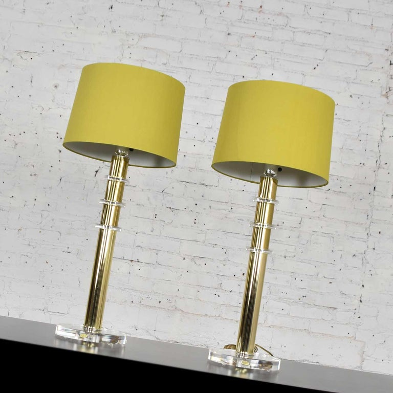 Fabulous vintage modern and rather Hollywood Regency brass plate and Lucite lamps with chartreuse green shades in the style of Karl Springer. The brass on this pair of lamps is nearly perfect and the Lucite has some age-appropriate wear including a
