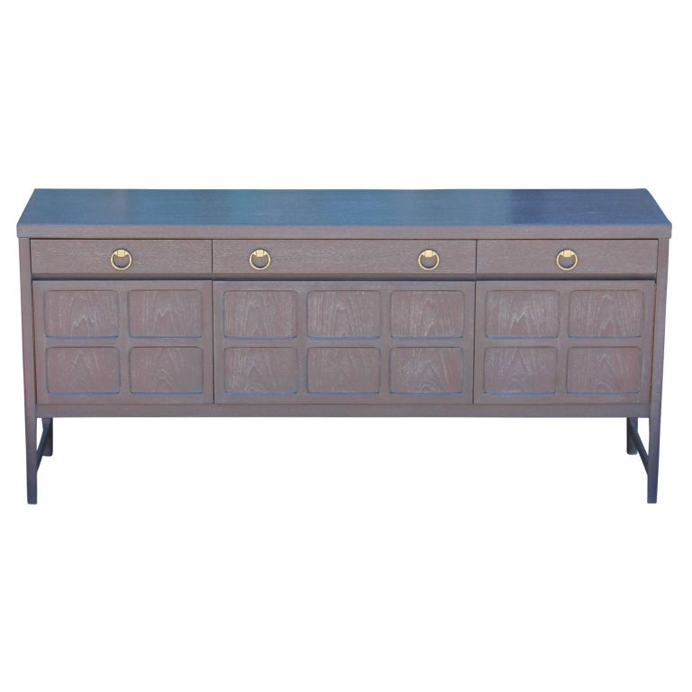 Wonderful modern / Hollywood Regency style sideboard with a grey cerused finish and outfitted with brass ring handles.  This credenza features three drawers at the top; one with dividers, making it easy to keep organized and shelving on the bottom.