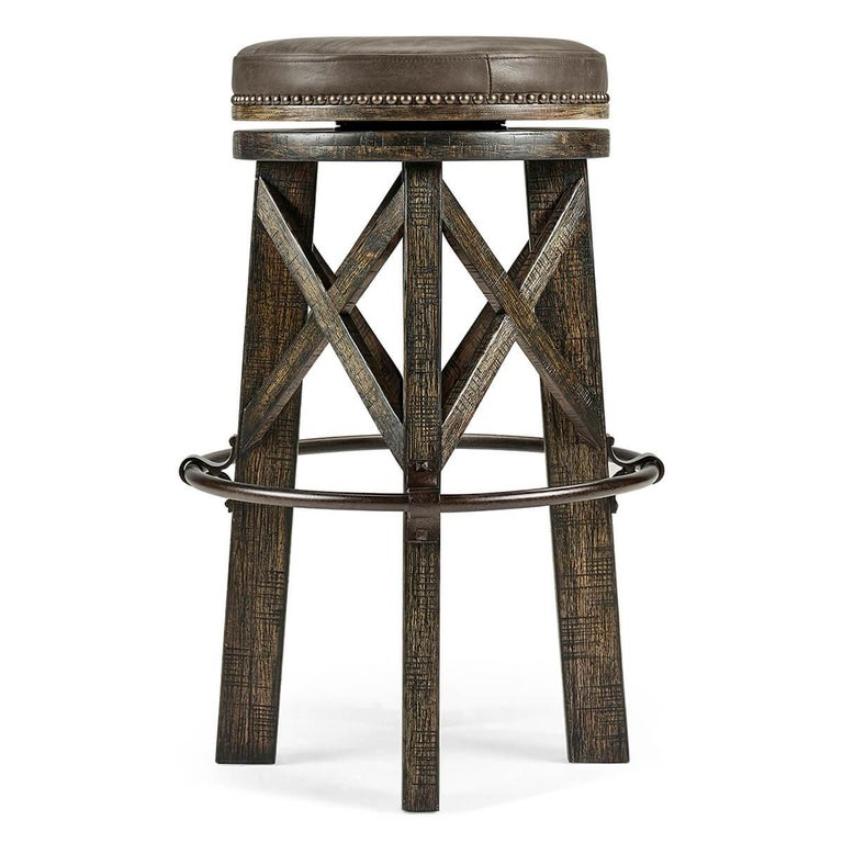 An Industrial modern solid dark driftwood round bar stool, the planked legs with exposed saw marks to the rustic finish, beneath a studded leather twist seat and an iron circular footrest.    Dimensions: 20
