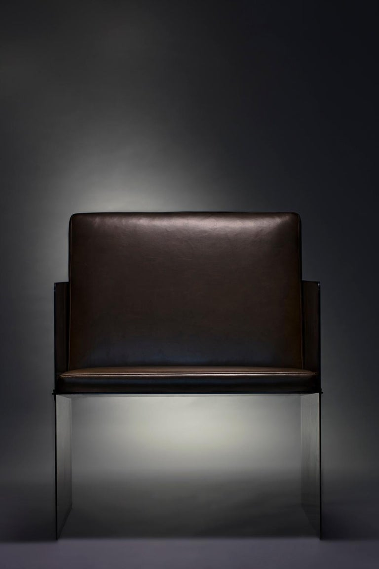Collection I: Plate chair  Constructed from bold steel plates and secured by bronze wedges, the plate chair is built to last. Resolute and refined, the deep black, hand-applied finish accentuates textural variations from the Industrial sheet