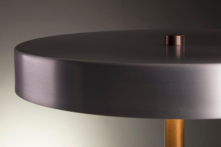 Collection I: Disc lamp in burnished aluminum  Available in a matte black or softly burnished finish, the shade of the disc lamp can either fade into its surroundings or catch light to emphasize its refined form.  The integrated dimmable LED