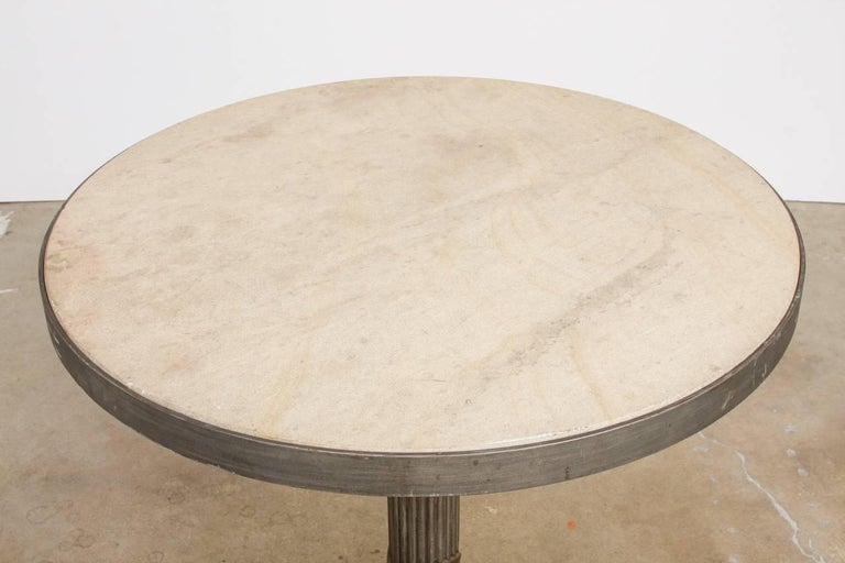 Bespoke modern iron and travertine limestone centre table or pub table made in a counter height size. 2 inch thick round disk of honed natural stone perfectly fit into an iron frame. Features a neoclassical style column support with a decorative