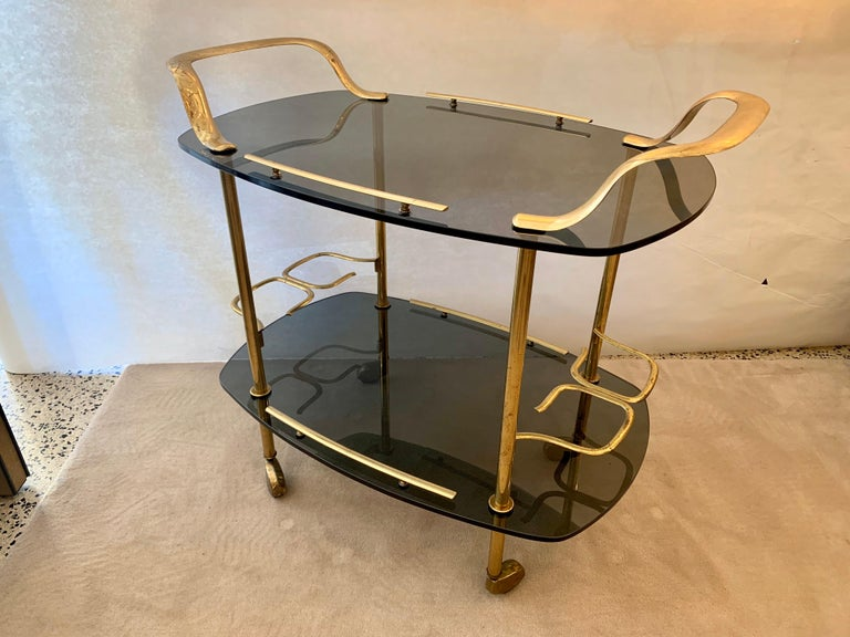 Fontana Arte attributed. bar cart with smoked gray glass (two tiers) and all brass fixtures including casters. Wonderful details and rolls easily.