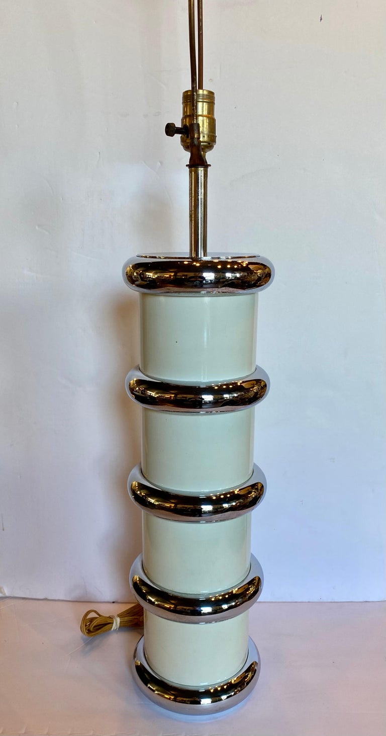 Mid-Century Modern chromed metal and enamel table lamp by Mutual Sunset Lamp Company. This tall round cylinder shaped lamp features an ivory/cream enamel column wrapped with stacked chromed metal bullnose rings. In the style of Karl Springer. Lamp
