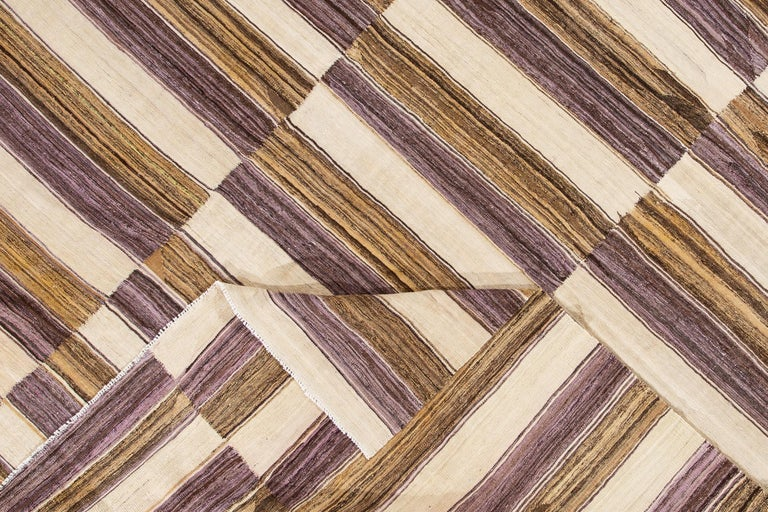 A handwoven modern Kilim rug with a linear geometric pattern design. This rug measures 10'0