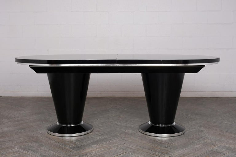 This modern style 1970s oval extendable dining room table features a rich black and silver stain combination with a lacquered finish. The table has a silver trim along the edge and pedestal bases. The removable leaf measures a 20.5 inches wide. This