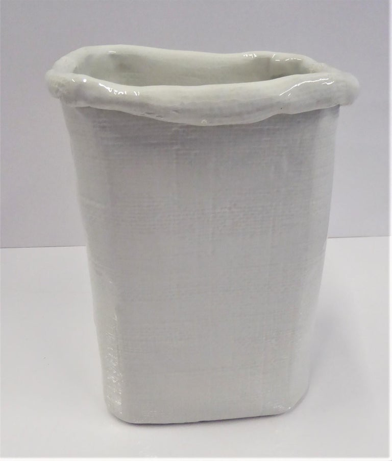 Italian Modern hand made ceramic white vase with a fluid free form shape representing a paper bag. A textured grid design on the outside with folds on the top edge and sides. The bottom incised with Made in ITALY 6494/33.  Measurements: Top- 7 1/2