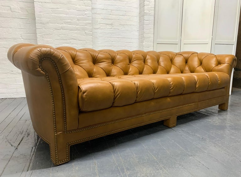 Modern leather chesterfield style sofa. Tufted leather sofa with brass nail-head trim.