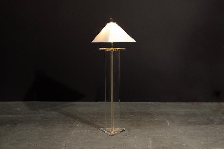 This beautiful lucite floor lamp by Marlee, circa 1970s, is signed and features a triangular shaped profile with matching lucite finial which lightly glows when the lamp is on. Comes with a simple pyramid shaped lampshade and wired for US outlets